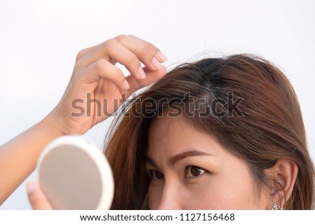 women are looking at the mirror to see the gray hair and hair loss problem ストックフォト ©