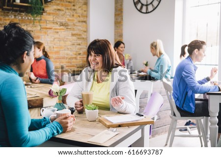 Women are sitting at a table in a cafe, socialising over coffee and tea. - Shutterstock ID 616693787