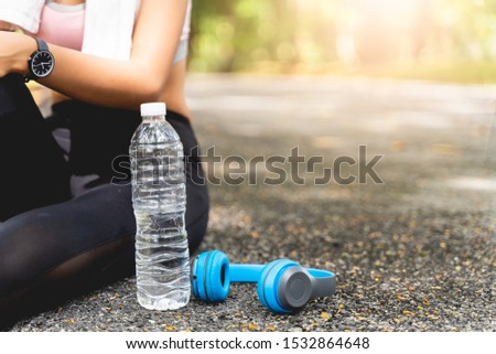 Women are sitting tired of their workouts, with water bottles and headphones on the side at the park with green leaves blur bokeh background in sport and healthy concept with copy space