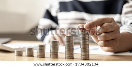 Women are stacking coins on top of the coin pile on the highest row. Placing coins in a row from low to high is comparable to saving money to grow more. Money saving ideas for investing in funds. Foto stock ©