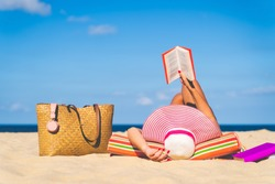 Women are sunbathing and read book on the beach there are bags and books on the side During the holidays in good weather and clear skies during summer, holidays and activities concept with copy space