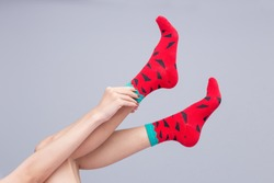 Women are wearing red socks. Gray background