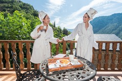 Women at a rural house having breakfast together. Homosexual couple enjoying a weekend rural getaway. Travel in Spain and europe with partner