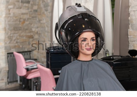 women at hairdresser while drying under hairdryer. Portrait of woman under hairdressing machine in parlor