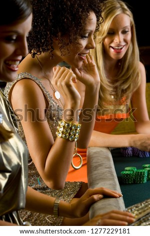 Women at roulette table in casino holding gambling chip at camera