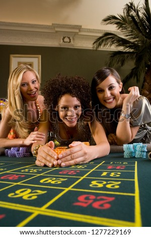 Women at roulette table in casino winning gambling chip at camera