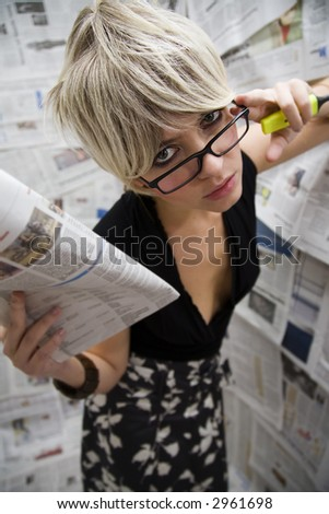 women at work: journalist standing against a wall full of articles