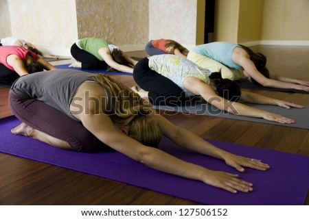 Women at yoga class bending forward on their yoga mats