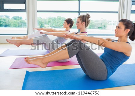 Women at yoga class in boat pose in fitness studio