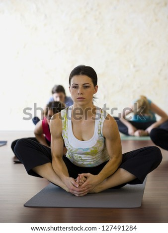 Women at yoga class sitting on the floor and stretching