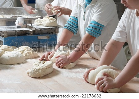 Women bakery team at work weigh and mixing dough - stock photo