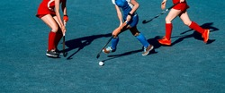 Women battle for control of ball during field hockey game. Team sport concept