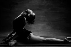 Women bending on her back. Yoga pose. Grainy. Shadows