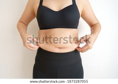 Women body fat belly. Obese woman hand holding excessive belly fat. diet lifestyle concept to reduce belly and shape up healthy stomach muscle. Foto stock ©