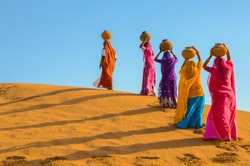 women carrying heavy jugs of water on their head and walking on a yellow sand dune in the hot summer desert against blue sky.water crises