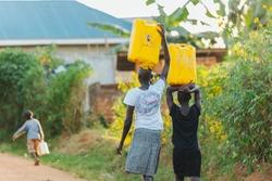 women carrying water cans in Uganda, Africa