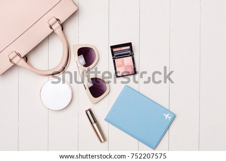 Women cosmetics and fashion items on table with camera and passport. Top view