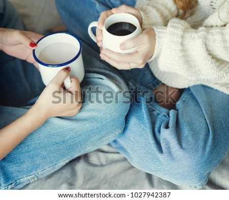 Women couple with hot drinks in winter
