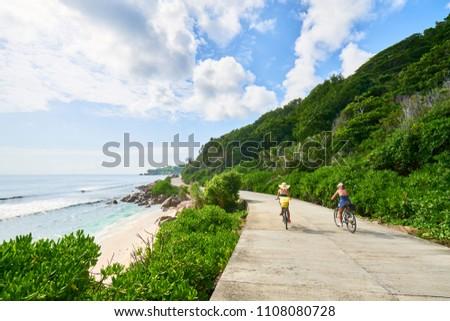 women cycling around the beautiful beaches, La Digue Island, Seychelles              Photo stock ©