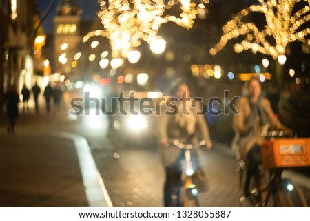 women cyclists ride down the street at night, bokeh and blur