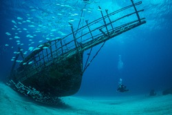 Women diver explores the wrecks at the Bridge dive site on the island of Sint Maarten, Dutch Caribbean