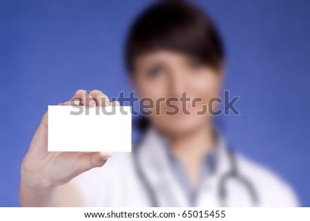 Women Doctor holding blank business card. Focus on fingers and card.