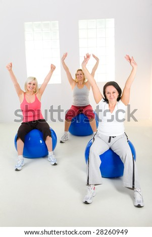 Women dresset sportswear working out on fitness ball. They have raised hands. They're smiling and looking at camera. Front view.
