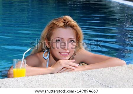 Women drinking cocktail in pool. Portrait of beautiful young women drinking cocktail on the poolside