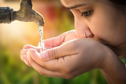 Women drinking tap water in outdoor.