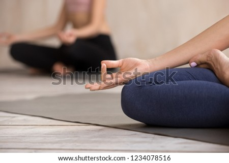 Women during group session meditate sitting in lotus position on yoga mat, close up focus on girl fingers folded in Jnana Mudra. Symbol concept of connection between human and the greater Universe