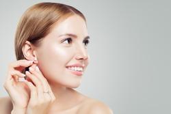 Women earring jewelry model. Cheerful woman with diamond earrings and ring, beautiful face closeup