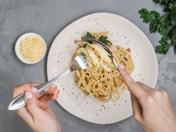 Women eating a plate of homemade carbonara with parsley, crisp bacon, cheese and garlic garnished on top at home. Hands twirl spoon fork to roll up spaghetti as Italian etiquette