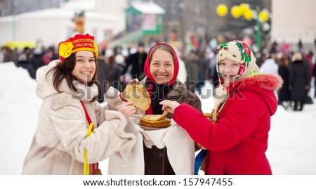 Women eating pancakes during  Maslenitsa festival in Russia