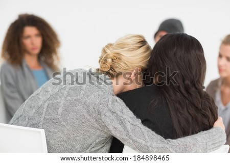 Women embracing in rehab group at therapy session