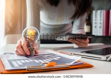 Women entrepreneurs use a tablet and laptop show creative business strategies with light bulbs as a concept.