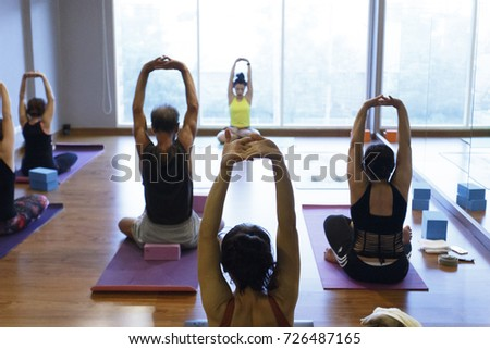 Women exercising in fitness studio yoga classes #726487165