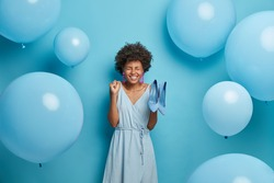 Women, fashion, clothes concept. Glad young African American woman clenches fist with joy, rejoices new purchase, buys fashionable outfit and shoes to dress for special occasion, blue color prevails