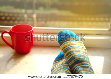 women feet with blue knitted socks on the window and blur red cup of coffee in the morning background  #1177079470