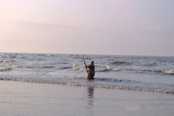 women fisher man fishing in beautiful morning tide on ganga sagar island sea ,bay of bengal