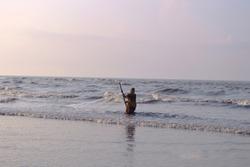 women fisher man fishing in beautiful morning tide on ganga sagar island sea ,bay of bengal