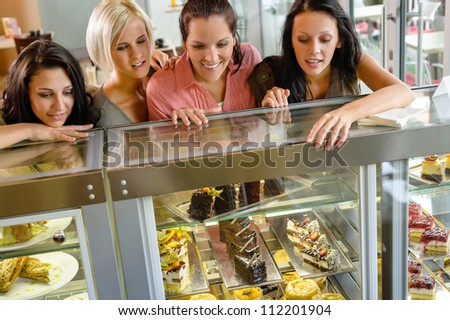 Women friends looking at cakes in cafe craving window display