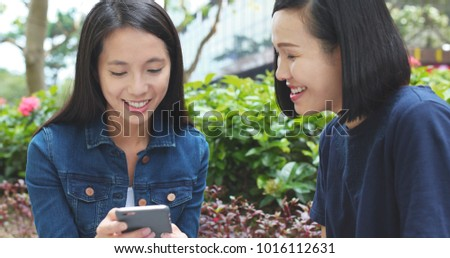 Women Friends watching on cellphone together at outdoor
