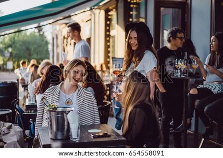 Women girlfriends in a summer cafe on the terrace drinking wine