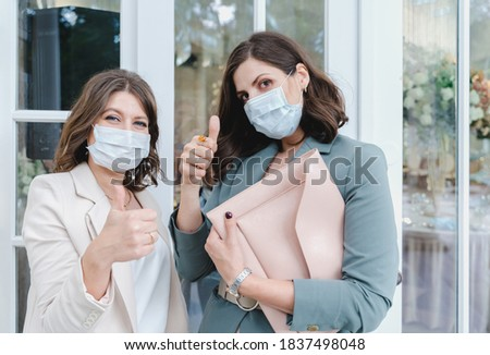 Women, girls in face masks in stylish suits at entrance to restaurant. Wedding organizers, event decorators, florists. Thumb up. Business meeting, negotiations, signing contract with client, customer. Stok fotoğraf ©
