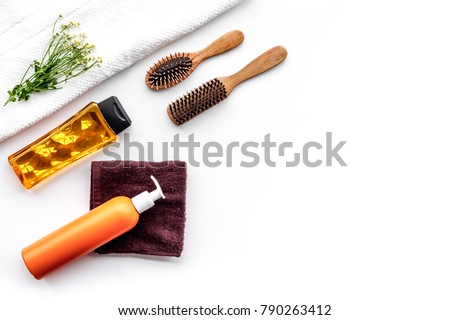 Women hair care set. Comb, shampoo, spray, towel on white background top view copy space