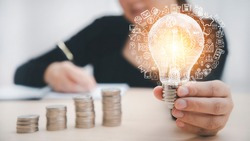 Women hand hold light bulb with icons work on the desk, Creativity and innovation are keys success. Concept of new idea and innovation with icons and light bulbs, working at home, Freedom of thought.