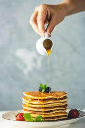 Women hand is pouring syrup from small ceramic jar to pancake with srtawberry, blueberry and mint in ceramic dish on a light wooden table and gray background.