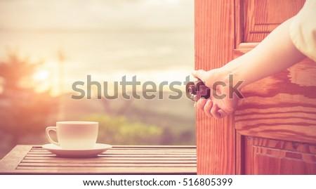 Women hand open door knob or opening the door view coffee espresso on wood table nature background in garden,warm tone
