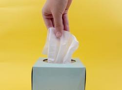 Women hand picking white napkin. white tissue paper from the blue tissue box