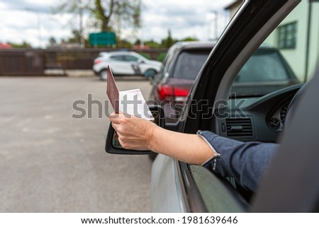 women hand through car window giving passport for customs control, driver with an identity card in a car at a border checkpoint Сток-фото ©